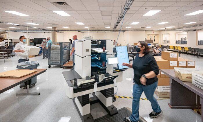 Varios empleados cuentan boletas en el Departamento de Elecciones del Condado de Maricopa en Phoenix, Arizona, el 5 de noviembre de 2020. (OLIVIER TOURON/AFP a través de Getty Images)
