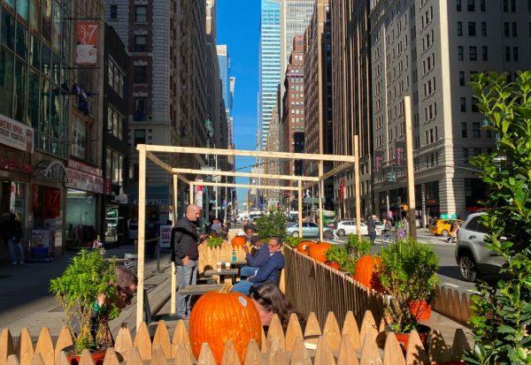 La gente disfruta de un almuerzo al aire libre en la 7th Avenue en Manhattan, Nueva York (EE.UU.), el 5 de noviembre de 2020. (Foto de DANIEL SLIM / AFP a través de Getty Images)