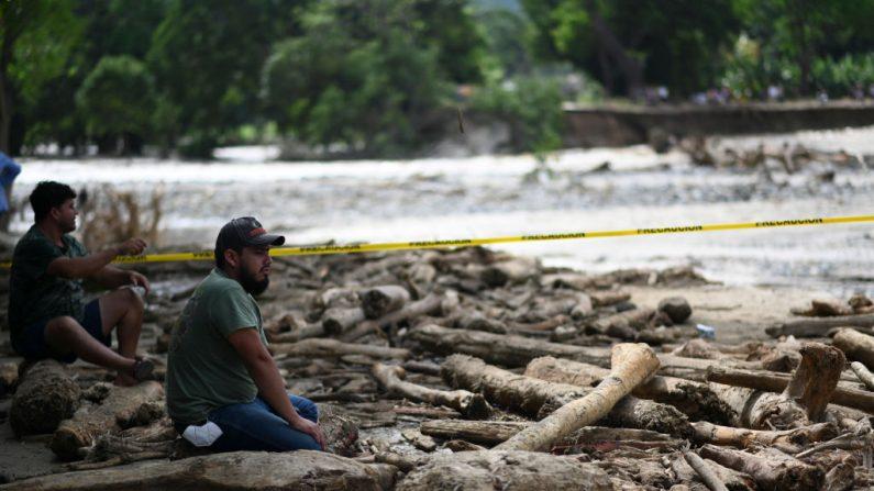 Hombres observan una excavadora que trabaja en una carretera inundada tras el paso del huracán Eta, ahora degradado a tormenta tropical, en Gualan, departamento de Zacapa, 154 km al norte de la Ciudad de Guatemala (Guatemala) el 7 de noviembre de 2020. (Foto de JOHAN ORDONEZ / AFP a través de Getty Images)