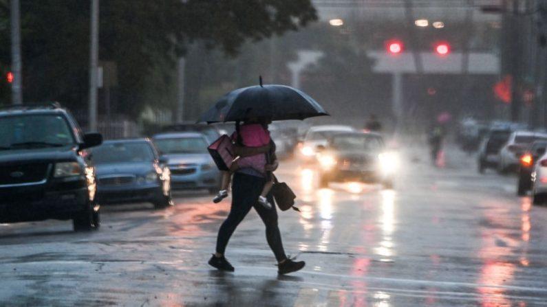 Un hombre sostiene a su hija mientras cruza la carretera durante una fuerte lluvia y viento cuando la tormenta tropical Eta se acerca al sur de Florida, en Miami, Florida, el 8 de noviembre de 2020. (Foto de CHANDAN KHANNA / AFP a través de Getty Images)