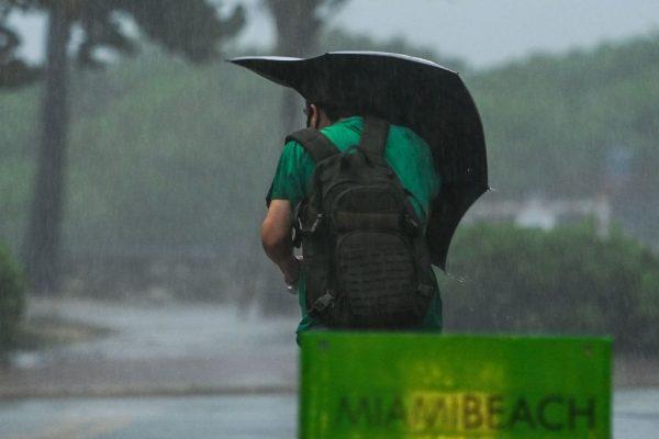 Un hombre camina en la calle durante fuertes lluvias y vientos cuando la tormenta tropical Eta se acerca al sur de Florida, en Miami, Florida el 8 de noviembre de 2020. (Foto de CHANDAN KHANNA / AFP a través de Getty Images)