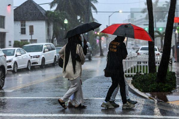 La gente cruza la calle durante una fuerte lluvia y viento mientras la tormenta tropical Eta se acerca al sur de Florida, en Miami, Florida el 8 de noviembre de 2020. (Foto de CHANDAN KHANNA / AFP a través de Getty Images)