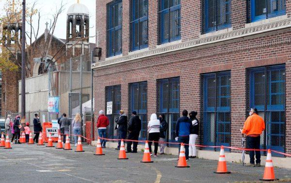 La gente espera en la fila para hacerse la prueba de covid-19 en el Centro de Pruebas Covid-19 de Ann Street School en Newark, Nueva Jersey, EE.UU., el 12 de noviembre de 2020. (Foto de TIMOTHY A. CLARY / AFP a través de Getty Images)