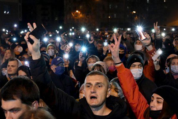 Los manifestantes hacen un signo de victoria y sostienen teléfonos con linternas para rendir homenaje a Román Bondarenko en el patio llamado 'La Plaza de los Cambios' en Minsk (Bielorrusia), a última hora del 12 de noviembre de 2020, un día después de que el activista de 31 años fuera golpeado por personas enmascaradas y muriera en el hospital. (Foto de STRINGER / AFP a través de Getty Images)