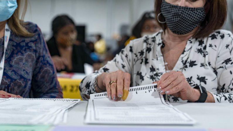 Los trabajadores del condado de Gwinnett comienzan el recuento de las boletas electorales el 13 de noviembre de 2020 en Lawrenceville, Georgia. La diferencia de votos entre el presidente de Estados Unidos, Donald Trump, y el candidato demócrata, Joe Biden, es mínima. (Foto de Megan Varner/Getty Images)
