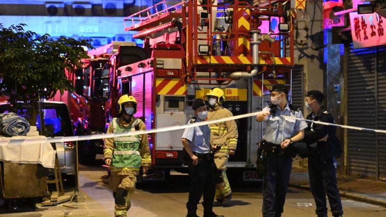 Agentes de policía y bomberos trabajan en el lugar de un incendio en Hong Kong a principios del 16 de noviembre de 2020, donde siete personas murieron y varias otras resultaron heridas. (Foto de PETER PARKS / AFP a través de Getty Images)