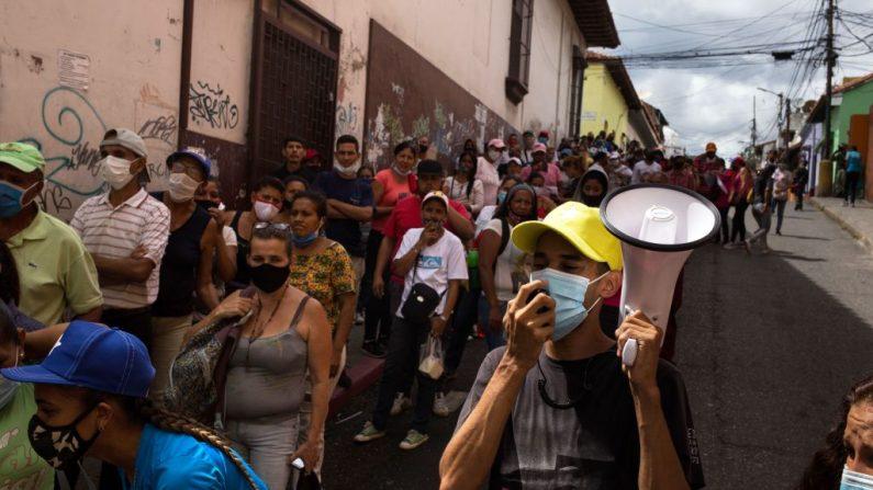 Un hombre (d) grita consignas políticas mientras la gente hace cola frente a la escuela pública José de Jesús Arocha en Petare, Caracas (Venezuela), durante una elección simulada para la próxima votación parlamentaria en Venezuela, el 15 de noviembre de 2020. (Foto de CRISTIAN HERNANDEZ / AFP vía Getty Images)