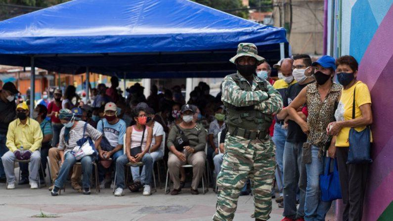 Los venezolanos esperan su turno para votar en la escuela pública José de Jesús Arocha en Petare, Caracas (Venezuela), durante una elección simulada para la próxima votación parlamentaria convocada por el chavismo, el 15 de noviembre de 2020, en medio de la pandemia del COVID-19. (Foto de CRISTIAN HERNANDEZ / AFP vía Getty Images)