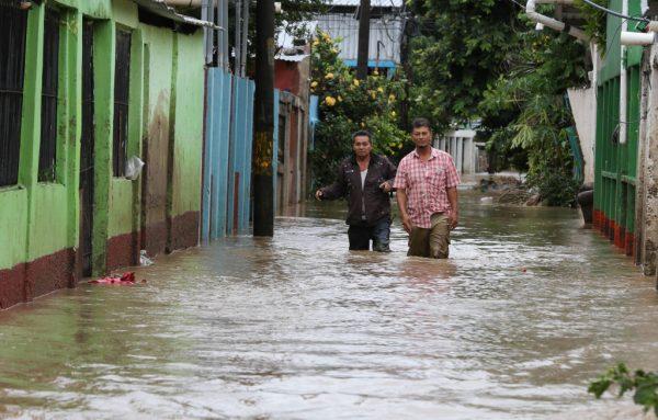 La gente vadea por una calle inundada por el desborde del río Chamelecón en el municipio de La Lima, departamento de Cortés, norte de Honduras, el 18 de noviembre de 2020, tras el paso del huracán Iota. (Foto de WENDELL ESCOTO / AFP a través de Getty Images)