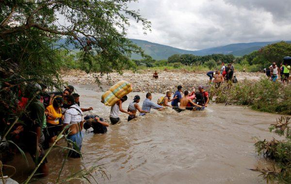 Los migrantes utilizan una cuerda para cruzar el río Táchira, la frontera natural entre Colombia y Venezuela, ya que la frontera oficial permanece cerrada debido a la pandemia de COVID-19 en Cúcuta, Colombia, el 19 de noviembre de 2020. (Foto de SCHNEYDER MENDOZA / AFP a través de Getty Images)