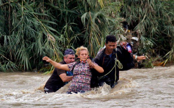 Se ayuda a una mujer a cruzar el río Táchira, la frontera natural entre Colombia y Venezuela, ya que la frontera oficial permanece cerrada debido a la pandemia de COVID-19 en Cúcuta, Colombia, el 19 de noviembre de 2020. Cientos de venezolanos varados en Colombia intentaron cruzar el puente internacional el 18 de noviembre de 2020, ya que las fuertes lluvias habían aumentado el nivel del río. (Foto de SCHNEYDER MENDOZA / AFP a través de Getty Images)
