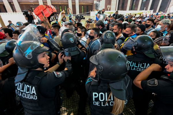 Los fans se enfrentan a la policía antidisturbios mientras intentan llegar al palacio presidencial de la Casa Rosada para rendir homenaje a la leyenda del fútbol argentino Diego Maradona en Buenos Aires, Argentina, el 26 de noviembre de 2020. (Foto de JUAN MABROMATA / AFP a través de Getty Images)