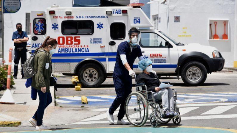 Un trabajador de la salud transfiere a una paciente en silla de ruedas al Hospital Universitario de La Samaritana el 28 de agosto de 2020 en Bogotá, Colombia. (Foto de Guillermo Legaria / Getty Images)