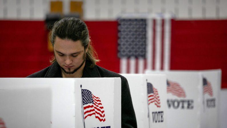 Un votante sin mascarilla llena su boleta, en Lansing, Michigan, el 3 de noviembre de 2020. (John Moore/Getty Images)