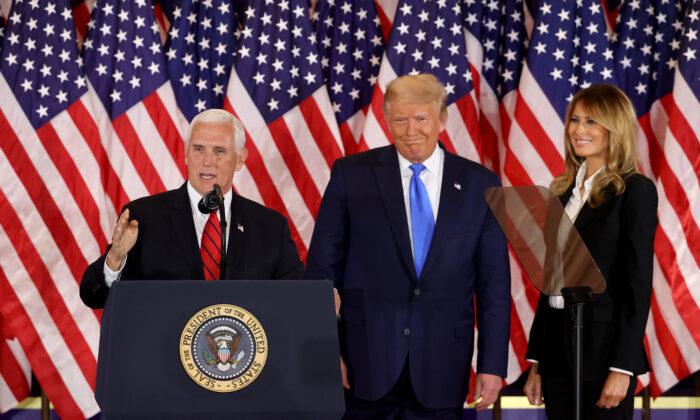 El vicepresidente Mike Pence habla mientras el presidente Donald Trump y la primera dama Melania Trump lo observan en la noche de las elecciones en el Salón Este de la Casa Blanca poco después de las 2 a.m. en Washington, D. C. el 4 de noviembre de 2020. (Chip Somodevilla/Getty Images)