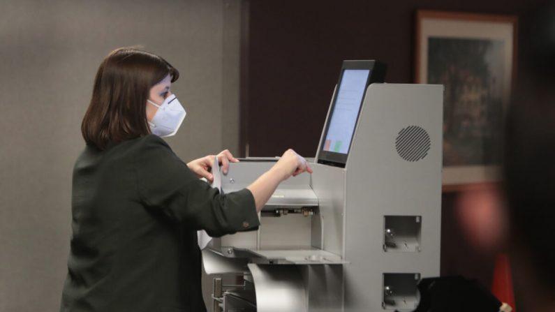 Una funcionaria electoral recopila el recuento de las boletas ausentes de una máquina de votación en Milwaukee, Wisconsin, el 4 de noviembre de 2020. (Scott Olson/Getty Images)