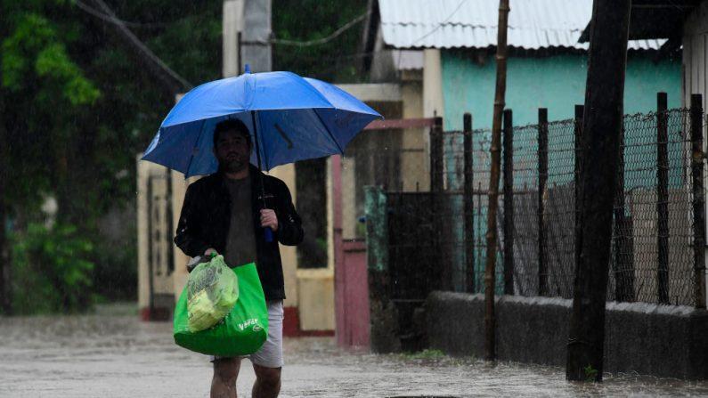Un vecino de La Democracia camina bajo la lluvia a través de una calle inundada después de los vientos y las lluvias traídas por la tormenta tropical Eta el 4 de noviembre de 2020 en Yoro, Honduras. (Foto de Yoseph Amaya / Getty Images)