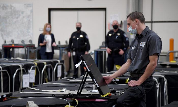 Trabajador electoral del condado de Clark revisa una máquina de votación entre otras que están encajonadas en el Departamento de Elecciones del condado de Clark en Las Vegas, Nevada, el 6 de noviembre de 2020. (Ethan Miller/Getty Images)