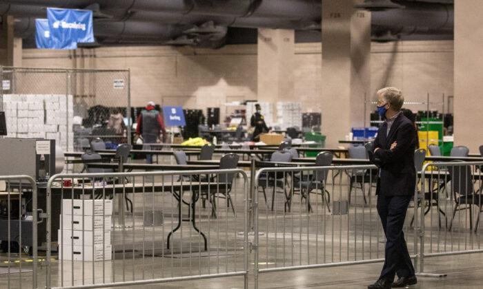 Un hombre observa desde el área de observadores mientras los trabajadores electorales cuentan las boletas en el Centro de Convenciones de Filadelfia en Filadelfia, Pensilvania, el 6 de noviembre de 2020. (Chris McGrath/Getty Images)