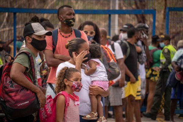 Una mujer con su familia llora mientras espera en la fila durante el proceso de evacuación por el huracán Iota el 21 de noviembre de 2020 en la isla de Providencia, Colombia. (Foto de Diego Cuevas / Getty Images)