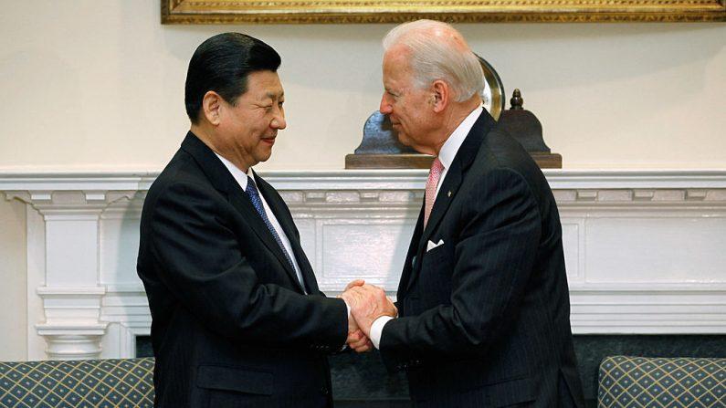 El entonces vicepresidente de Estados Unidos Joe Biden (der) y el líder del régimen chino Xi Jinping se dan la mano antes de una reunión bilateral en la Sala Roosevelt de la Casa Blanca el 14 de febrero de 2012 en Washington, DC. (Chip Somodevilla/Getty Images)