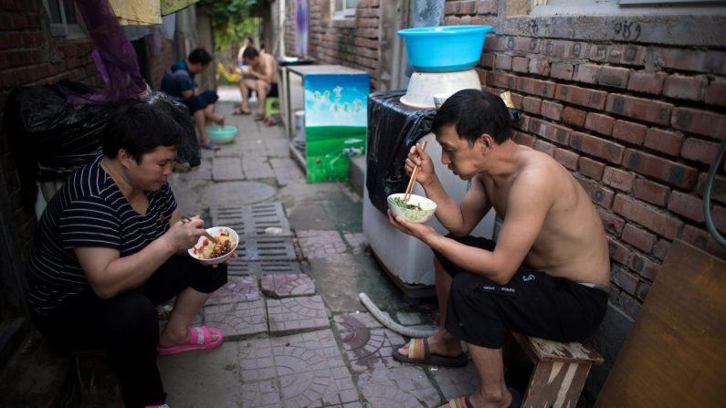 La gente cena fuera de sus habitaciones en una calle de un pueblo de migrantes en las afueras de Beijing el 17 de agosto de 2017. (NICOLAS ASFOURI/AFP/Getty Images)