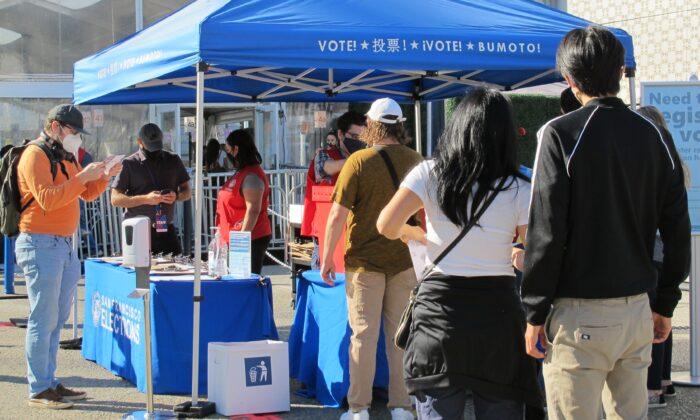 La gente deja sus boletas electorales en un puesto cerca del Auditorio Cívico Bill Graham en San Francisco el 31 de octubre de 2020. (Ilene Eng/The Epoch Times)
