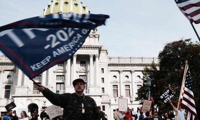 Docenas de personas que piden se detenga el conteo de votos en Pensilvania debido a un presunto fraude contra el presidente Donald Trump se reúnen en las escaleras de la capital del estado en Harrisburg, Pensilvania, el 5 de noviembre de 2020. (Spencer Platt/Getty Images)