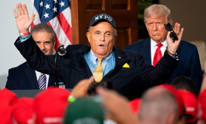 El presidente de Estados Unidos, Donald Trump (der.), escucha mientras su abogado personal, Rudy Giuliani, habla ante la Asociación Benevolente de la Policía de la Ciudad de Nueva York, en el Trump National Golf Club, en Bedminster, Nueva Jersey, el 14 de agosto de 2020. (Jim Watson/AFP a través de Getty Images)