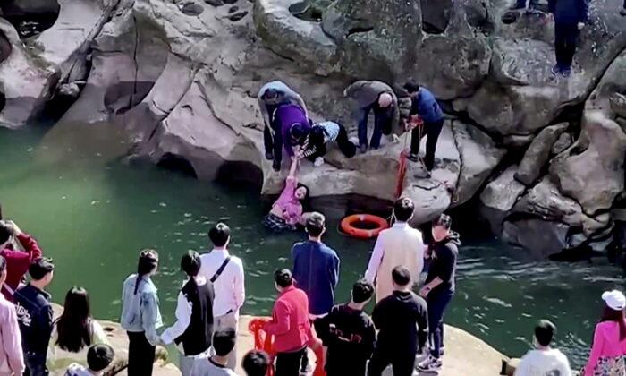 En esta captura de pantalla tomada de un vídeo, Stephen Ellison, cónsul general británico en Chongqing, rescata a una estudiante que se estaba ahogando en un lugar pintoresco en Chongqing, China, el 14 de noviembre de 2020. (Jiang Lang vía el consulado británico en Chongqing/vía Reuters TV)