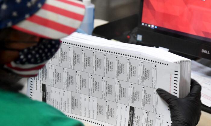 Un trabajador electoral del condado de Clark escanea las boletas por correo en el Departamento de Elecciones del condado de Clark, en North Las Vegas, Nevada, el 7 de noviembre de 2020. (Ethan Miller/Getty Images)