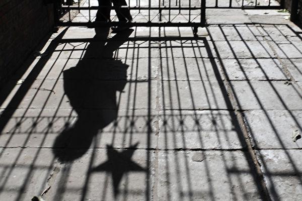Una mujer camina entre una puerta de metal adornada con una insignia de estrella comunista en un antiguo complejo residencial de Beijing en la mañana del 15 de noviembre de 2008. (FREDERIC J. BROWN/AFP/Getty Images)