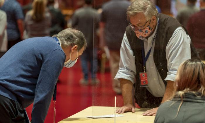 Un representante del presidente Donald Trump (i) mira una boleta durante el recuento de votos del Condado de Dane en Madison, Wisconsin, el 20 de noviembre de 2020. (Andy Manis/Getty Images)
