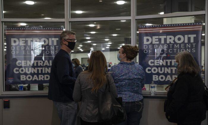 Observadores electorales miran a través de una ventana después de que se les dijo que la capacidad de observadores electorales se había cumplido por ahora en la Junta Central de Conteo en el TCF Center en Detroit, Michigan, el 4 de noviembre de 2020. (Elaine Cromie/Getty Images)