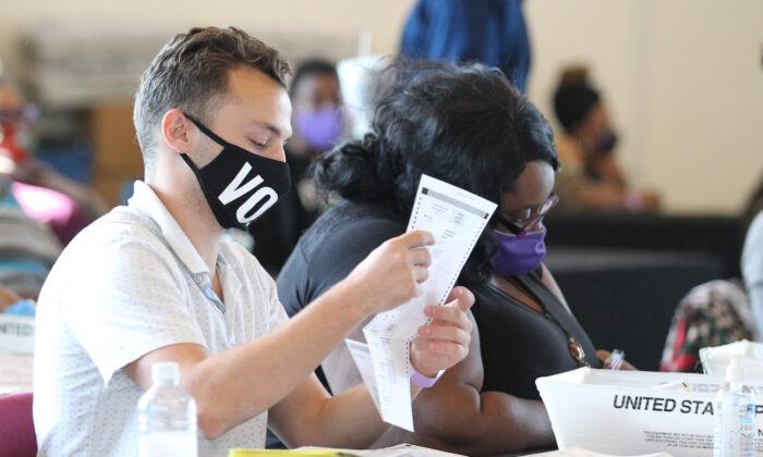 Varios empleados del Condado de Fulton examinan las boletas durante el recuento de votos en el State Farm Arena en Atlanta, Georgia, el 5 de noviembre de 2020. (Tami Chappell /AFP vía Getty Images)