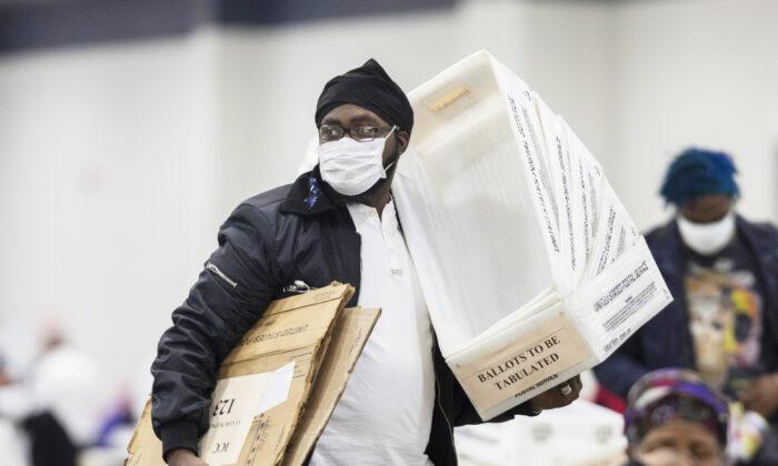 Un trabajador del Departamento de Elecciones de Detroit lleva cajas vacías que se utilizan para organizar los votos en ausencia después de acercarse al final del recuento de votos en la Junta Central de Conteo en el Centro TCF en Detroit, Mich., el 4 de noviembre de 2020. (Elaine Cromie/Getty Images)