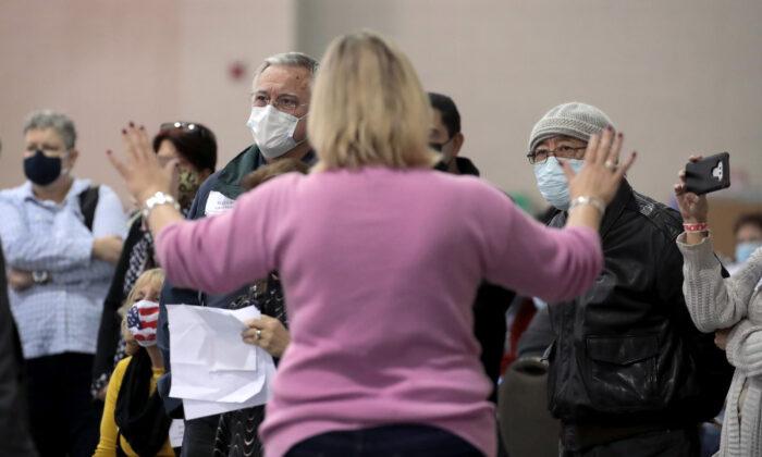 Una funcionaria electoral calma a los observadores indisciplinados mientras se discuten cuestiones de procedimiento durante el proceso de reconteo de votos, en el Centro de Wisconsin en Milwaukee, Wisconsin, el 20 de noviembre de 2020. (Scott Olson/Getty Images)