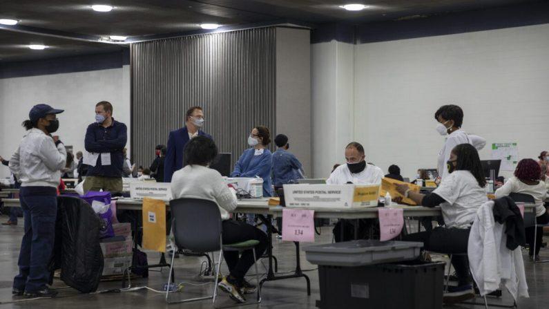 Los opositores a las encuestas observan a los trabajadores del Departamento de Elecciones de Detroit inspeccionar y clasificar las boletas de voto ausente en la Junta Central de Conteo en el Centro TCF en Detroit, Michigan, el 4 de noviembre de 2020. (Elaine Cromie/Getty Images)