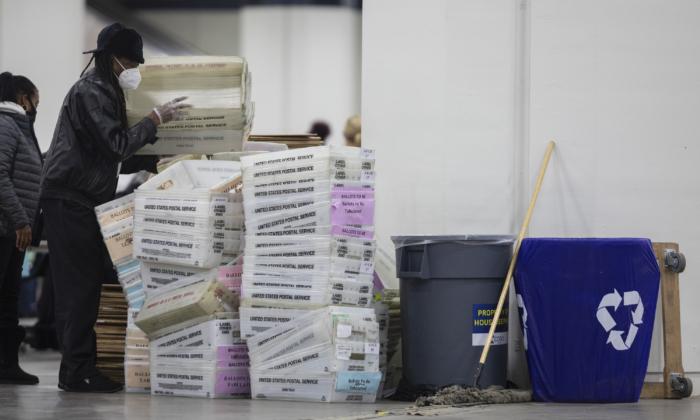 Un trabajador del Departamento de Elecciones de Detroit ayuda a apilar las cajas vacías utilizadas para organizar los votos en ausencia después de acercarse el final del recuento de votos en ausencia en la Junta Central de Conteo en el Centro TCF en Detroit, Michigan, el 4 de noviembre de 2020. (Elaine Cromie/Getty Images)