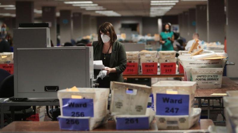 Claire Woodall-Vogg, directora ejecutiva de la comisión electoral de Milwaukee recoge el recuento de los votos en ausencia de una máquina de votación el 4 de noviembre de 2020 en Milwaukee, Wisconsin. (Scott Olson/Getty Images)