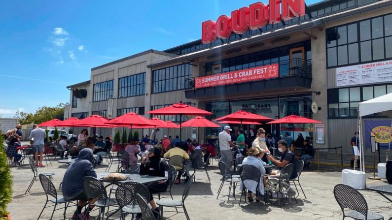 La gente disfruta del almuerzo en un área al aire libre llena de gente en un restaurante en el Pier 45 de San Francisco (California) el 2 de agosto de 2020. (Foto de DANIEL SLIM / AFP a través de Getty Images)