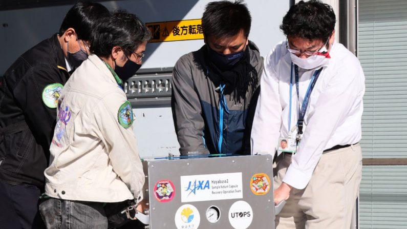 Miembros de la agencia aeroespacial de Japón cargan una caja que contiene la cápsula separada de la sonda espacial Hayabusa2 en el campus de Sagamihara de la Agencia de Exploración Aeroespacial de Japón en la prefectura de Kanagawa el 8 de diciembre de 2020. (Foto por STR / JIJI PRESS / AFP a través de Getty Images)