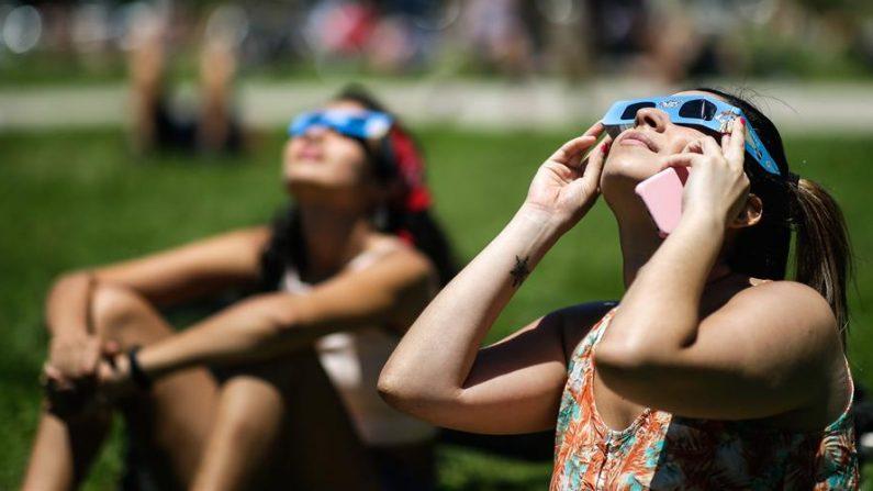 Personas observan el eclipse solar con lentes especiales, desde los exteriores del Planetario el 14 de diciembre de 2020, en Buenos Aires (Argentina). EFE/ Juan Ignacio Roncoroni