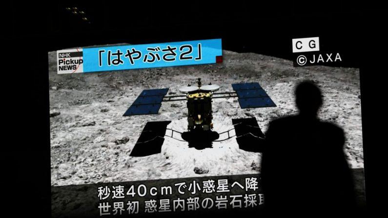 En esta imagen tomada el 10 de julio de 2019, un hombre pasa junto a una pantalla que muestra una imagen generada por computadora de la sonda Hayabusa2, durante una transmisión de noticias en el distrito de Akihabara en Tokio (Japón). (Foto de BEHROUZ MEHRI / AFP a través de Getty Images)