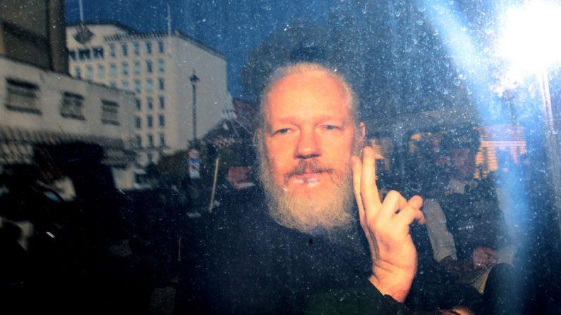 Julian Assange saluda desde un vehículo de la policía a su llegada a la corte Westminster Magistrates el 11 de abril de 2019 en Londres, Inglaterra. (Jack Taylor/Getty Images)