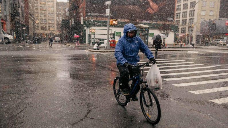 Un trabajador de entrega monta una bicicleta en Houston Street durante la primera tormenta de nieve del invierno en Manhattan el 2 de diciembre de 2019 en Nueva York, Estados Unidos. (Foto de Scott Heins / Getty Images)