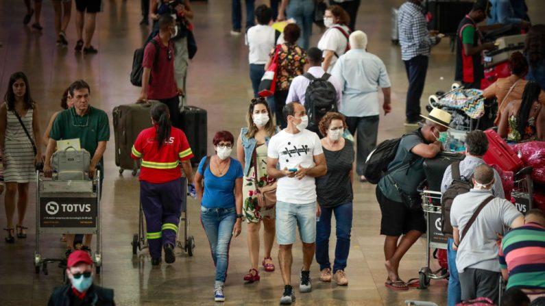 Unos pasajeros caminan con mascarillas en el Aeropuerto Internacional de Guarulhos el 14 de marzo de 2020 en Sao Paulo, Brasil. (Foto de Rodrigo Paiva / Getty Images)