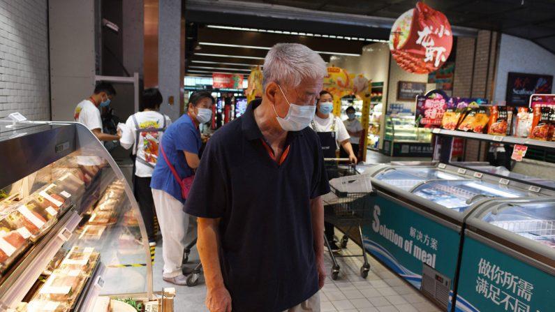 Un hombre compra en la sección de carnes y mariscos de un supermercado en Beijing el 17 de junio de 2020. (GREG BAKER/AFP a través de Getty Images)
