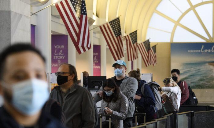 Los pasajeros esperan en la fila para ingresar a un punto de control de la Administración de Seguridad de Transporte, en el Aeropuerto Internacional de Los Ángeles, en Los Ángeles, California, el 25 de noviembre de 2020. (PATRICK T.FALLON/AFP a través de Getty Images).