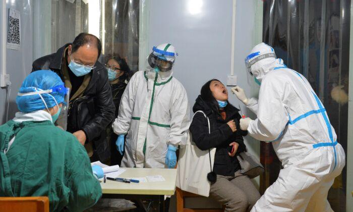 Trabajadores de la salud realizan pruebas de ácido nucleico en residentes de Chengdu, provincia de Sichuan, suroeste de China, el 8 de diciembre de 2020. (STR/AFP a través de Getty Images)